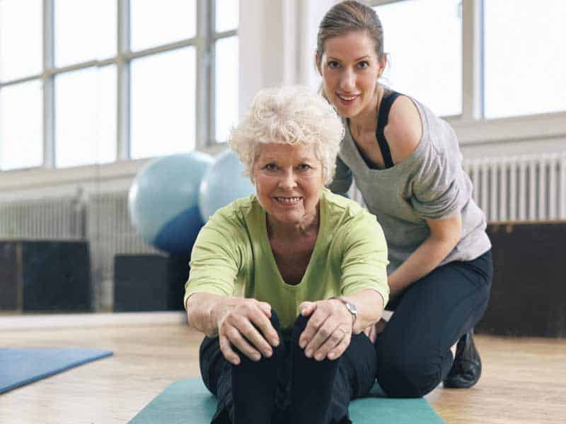 personal trainer helps senior stretch during one-on-one session