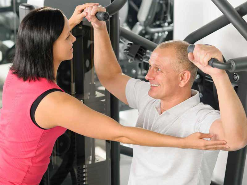female trainer shows a male client how to use a strength training machine