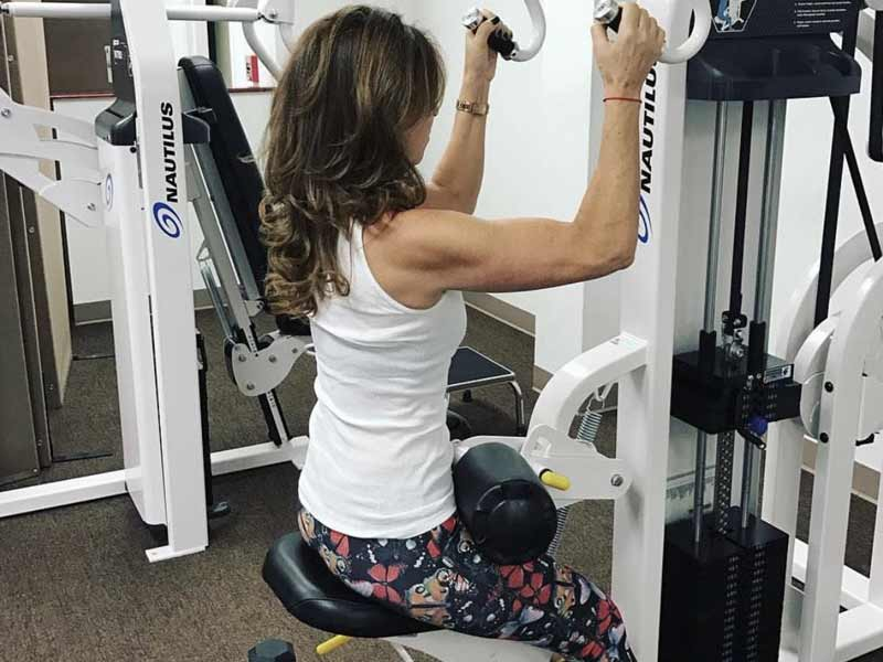 woman uses strength training machine at a personal training studio