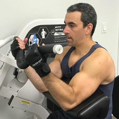 Man doing bicep curls on a machine at Loyalty Fitness in Syosset, NY