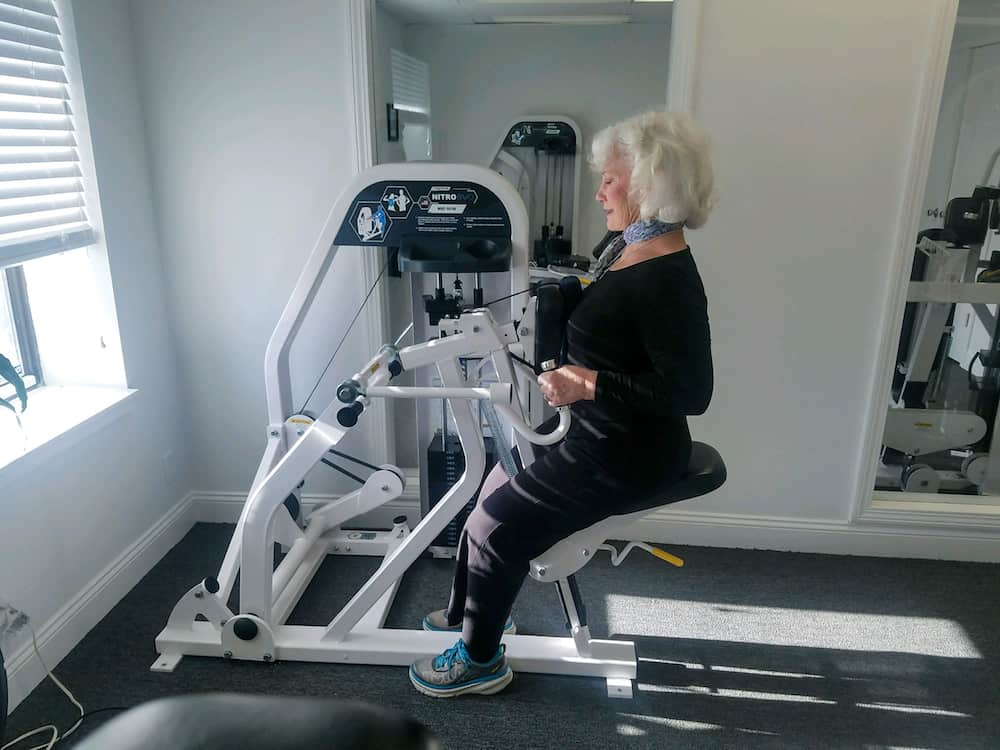 woman using row machine in gym