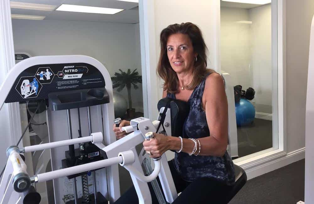 woman using strength training machine in private fitness studio