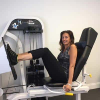 Gail Fennell, MD, working out on a leg machine at Loyalty Fitness