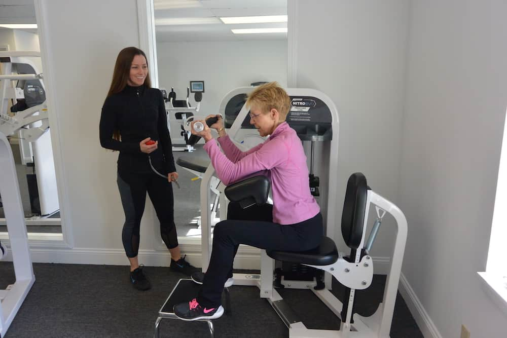 trainer assisting older woman using strength training machine