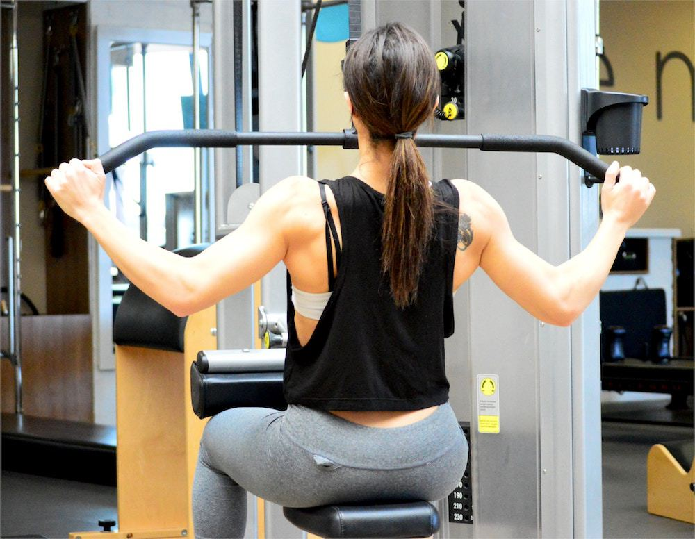 woman pulling on bar of weight lifting machine