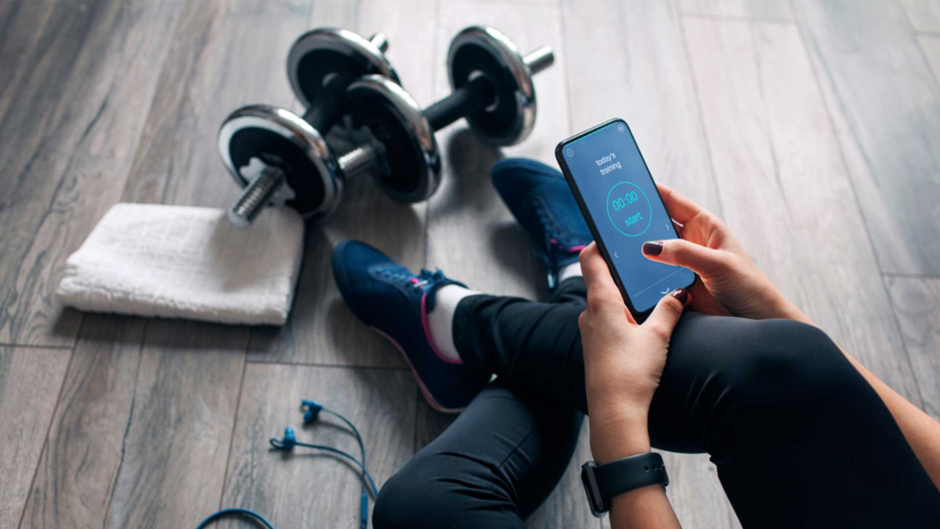 Woman sitting on the floor of a gym looking at her cell phone